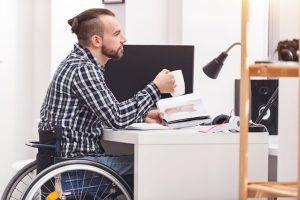 disabled man in a wheelchair drinking coffee and holding a book at his desk