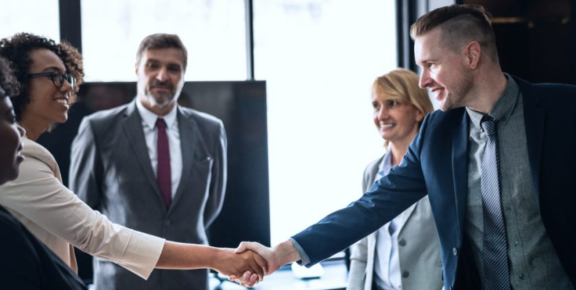 group of business people with a man and woman shaking hands